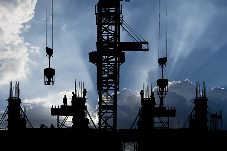 Silhouette of construction site & workers with ray of the light background