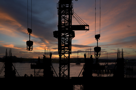 Silhouette of construction site & workers with twilight background Stock Photo