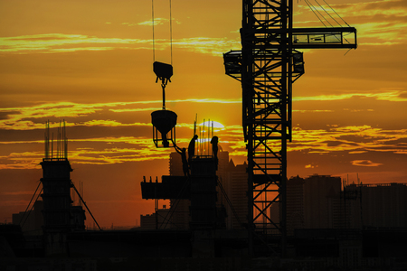 Silhouette of construction site & workers with sunset vibrant sky background