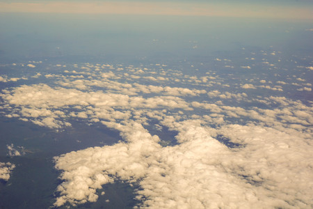 The sky and clouds and the view seen in the window of the plane