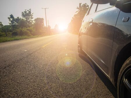 The car parked on the side of the road with sunlight shining from behind, concept of increasing strength in business. Stok Fotoğraf