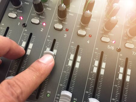 The male hand makes the sound adjustment on the audio mixer. Stok Fotoğraf