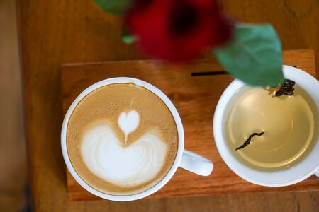Heart-shaped coffee on a brown wood table.