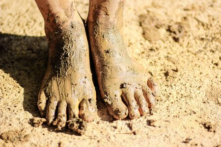 A young Asian girl was playing in mud and the feet were stained with mud. Stockfoto