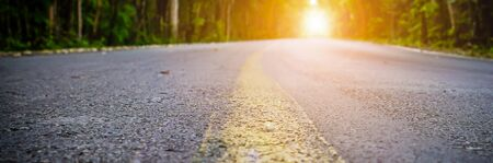 Banner size,The road in the morning forest with sunshine at the destination.