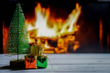 Small Christmas trees and Christmas presents that are behind the fireplace.