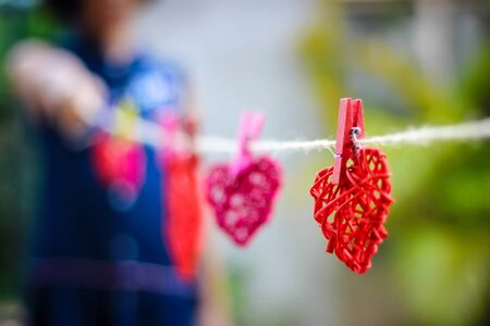 The red rattan heart hung with a child holding the other end of the rope.