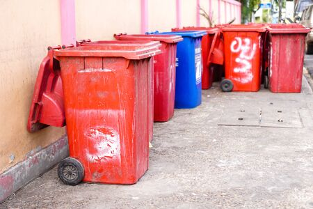 Old red trash is located beside the road.