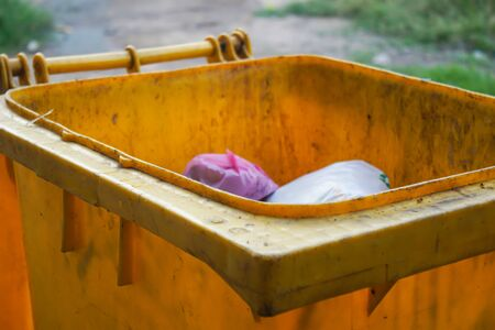 Old yellow trash is located beside the road. Stockfoto