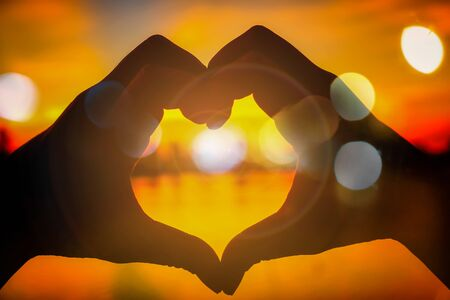 Love silhouette hand shape in the evening sunset time concept valentines day.