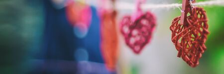 Size banner, red rattan heart hung with a childs hand holding the other end of the rope Valentines Day concept