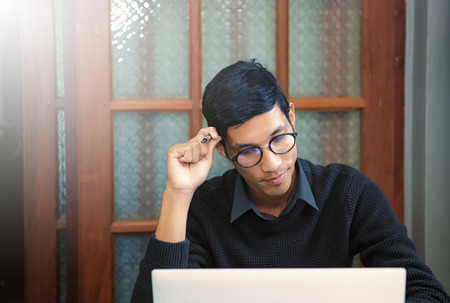 Student studying and writing notes in a notebook sitting at a desk at home