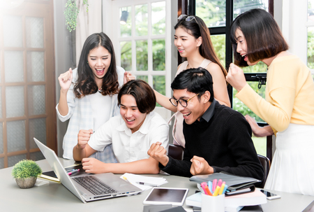 group of young asian student discussing about interesting things in laptop at coworking space.