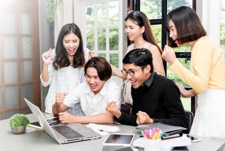 Gruppe des jungen asiatischen Studenten, der über interessante Sachen im Laptop am coworking Raum sich bespricht.