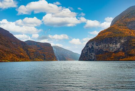 A view on the Songefjorden (King of the Fjords) from the water level. It is the deepest fjord in Norway. Tall, lush green mountains surrounding the fjord. Calm surface of the water. Clear blue sky.