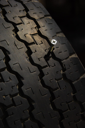screw jammed in old tire Stock Photo - 25866144