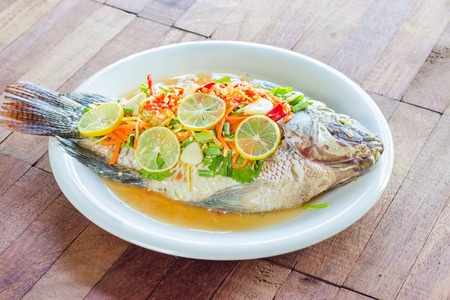 steamed Nilotica fish,thai style steamed fish in spicy sauce,wood background