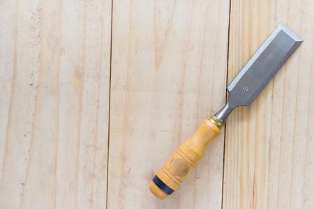 carpenter chisel on wood background