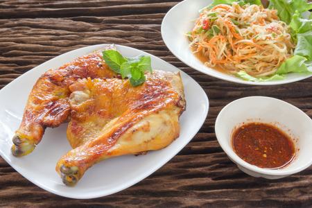 anima: grilled chicken with papaya salad,wood background