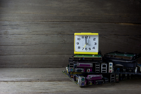 computer transistors: alarm clock with circuit Boards on wood background, still life