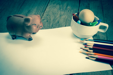 piggy bank: crayons and piggy bank on a sheet of paper,vintage effect filter Stock Photo