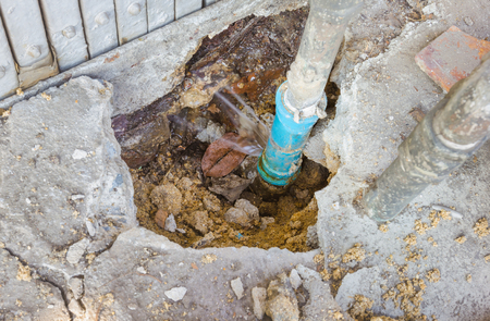 Water leaks from underground blue pipes.