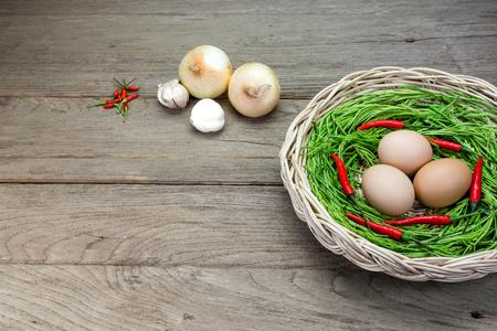 cha om: Acacia pennata and egg in basket on wood background Stock Photo