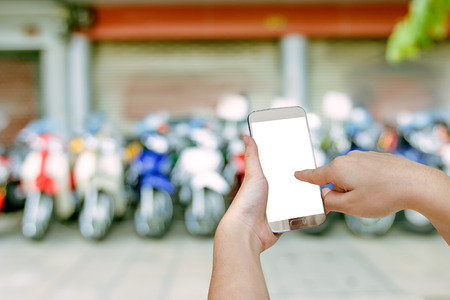 hand holding mobile smart phone with blurry showroom motorcycle background