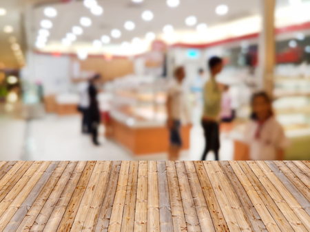 Wooden table with shopping mall blurred background