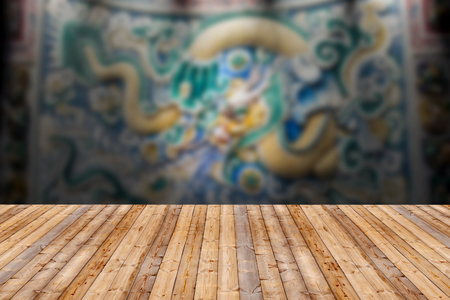 website background: Wooden table with dragon statue wall blurred background Stock Photo