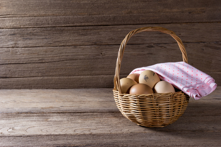 eggs in a wicker basket on wooden table
