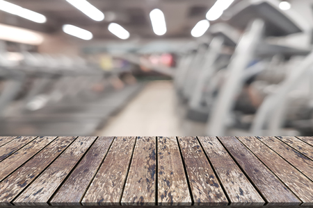 Empty wooden board space platform with blur fitness gym equipment background