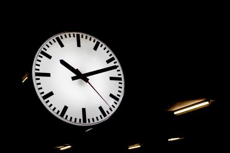 big timer: White clock in the dark Stock Photo