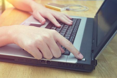Zet schakelaarlaptop op bureau, close-upmens aan die notitieboekje op houten lijst gebruiken