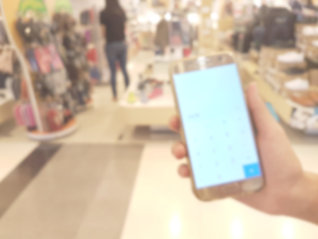 hand holding mobile smart phone in shopping mall,blur background Stock Photo