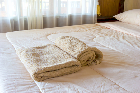 fresh brown towels on bed