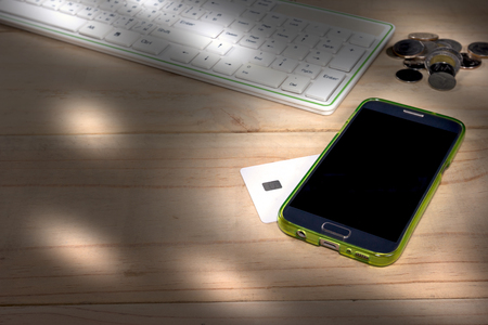smart phone and credit card on wooden table
