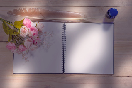 open note book with feather pen on the wood table