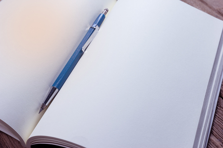 closeup open note book with clutch-type pencil on wood background Stock Photo