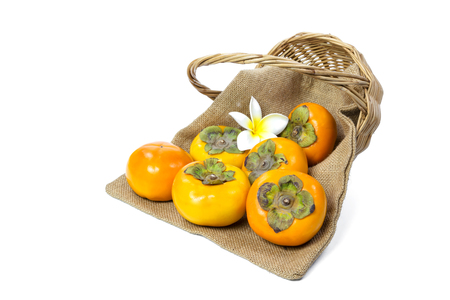 Persimmon with sack and wicker basket isolated on white background Stock Photo