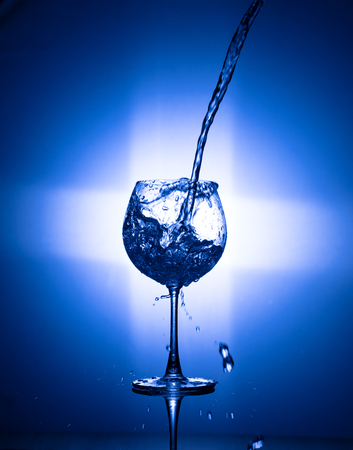 Pouring water in to the wine glass with rear light on blue background