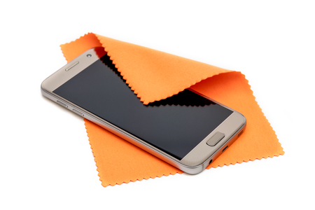 Smartphone cleaning dirty screen with orange fabric,isolated on white background Foto de archivo