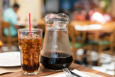 cola water and ice in glass with jar in restaurant