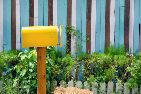 yellow vintage mailbox with wooden wall in garden
