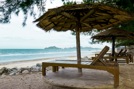 empty chairs and wooden umbrellas on a sandy beach