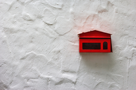 red mailbox on white concrete wall Stock Photo