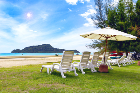 White beach chair and umbrella on tropical beach with blue sky
