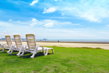 White beach chair on tropical beach with blue sky