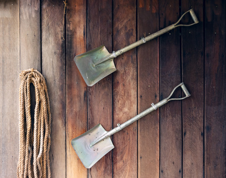 Shovel on old wooden wall background. Stock Photo