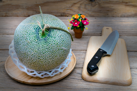 melon and knife on cutting board